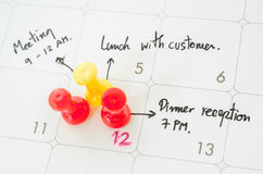 Pushpin on calendar with busy day. Stock Photo