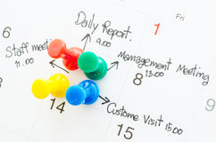 Pushpin on calendar with busy day. Stock Photos