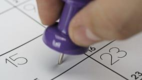 Pushpin on calendar stock footage