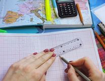 Pushpin on the economic chart. World map on the table of travelers,the hand holding the handle and chooses a new place to travel,a lot of pens and stationery Royalty Free Stock Photography