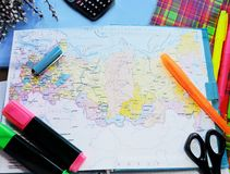 Pushpin on the economic chart. World map on the table of travelers,the hand holding the handle and chooses a new place to travel,a lot of pens and stationery Royalty Free Stock Images
