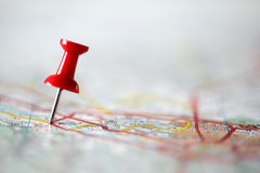 Pushpin on map. Red pushpin showing the location of a destination point on a map Stock Photography