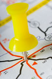 Pushpin on Map. Yellow pushpin on map marking an intersection of several roads Stock Photo