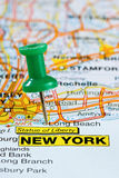 Pushpin in New York Map. City of New York highlighted with a green push pin on an atlas or map Royalty Free Stock Photo
