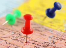 Pushpin pointing place on a paper map. Close up of Pushpins pointing place on a paper map Royalty Free Stock Photo