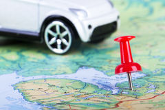 Pushpin and Toy Car on Map. Pushpin and small, toy car on map for travel concept Royalty Free Stock Photo