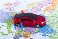 Pushpin and Toy Car on Map. Pushpin and small, toy car on map for travel concept Royalty Free Stock Image