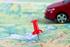Pushpin and Toy Car on Map. Pushpin and small, toy car on map for travel concept Royalty Free Stock Images
