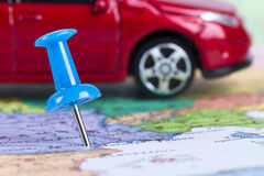 Pushpin and Toy Car on Map. Pushpin and small, toy car on map for travel concept Stock Photography