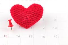 Pushpins на календаре и красном сердце Стоковое Фото