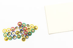 Pushpins aiming note paper. Arrow made from coloured pushpins aiming note paper on a white background Royalty Free Stock Photo