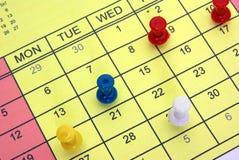 Pushpins on calendar. Pushpins on a yellow calendar Royalty Free Stock Photography