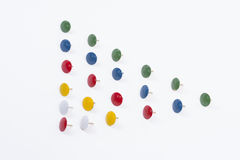 Pushpins. Colored pushpins into a triangle royalty free stock photography