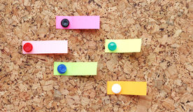 Pushpins holding note papers on board Stock Images