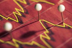 Pushpins mark stock price. On red background Royalty Free Stock Photography