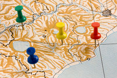 Pushpins on Nameless Map. Shot of colored pushpins on nameless geographic map printed on paper Royalty Free Stock Photo