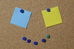 Pushpins and notes on board. Pushpins and colored notepaper on cork poster board stock photo