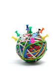 Pushpins on Rubberband Ball. On White Background Royalty Free Stock Photos