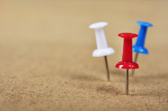 Pushpins on wooden background Royalty Free Stock Photo