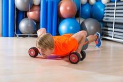 白肤金发的人健身房俯卧撑pushup哑铃 图库摄影