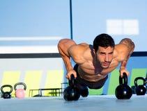 Pushup da força do impulso-acima do homem do Gym com Kettlebell Imagem de Stock Royalty Free