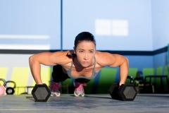 Pushup da força do impulso-acima da mulher do Gym com dumbbell Fotografia de Stock