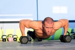 Pushup de la fuerza del pectoral del hombre del gimnasio con pesa de gimnasia Imagen de archivo libre de regalías
