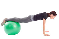 Pushup Exercise with Gym Ball. Young woman with gym ball doing pushup exercise, isolated on white background Royalty Free Stock Images