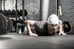 Pushup workout in gym. Athletic guy with a beard prepares to make a pushup in the gym on the gray brick wall background. He wears sportswear, white sneakers and royalty free stock photos