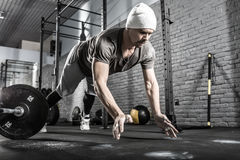 Pushup workout in gym. Cool guy with a beard makes a pushup with a front clap in the gym on the gray brick wall background. He wears sportswear, white sneakers stock photography