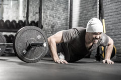 Pushup workout in gym. Muscular guy with a beard makes a pushup in the gym on the gray brick wall background. He wears sportswear, white sneakers and a white cap royalty free stock photography