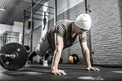 Pushup workout in gym. Nice guy with a beard prepares to make a pushup in the gym on the gray brick wall background. He wears sportswear, white sneakers and a royalty free stock photography