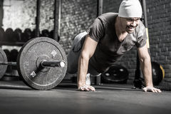 Pushup workout in gym. Powerful guy with a beard makes a pushup in the gym on the gray brick wall background. He wears sportswear, white sneakers and a white cap stock photo