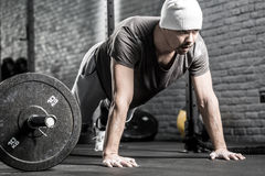 Pushup workout in gym. Sportive guy with a beard prepares to make a pushup in the gym on the gray brick wall background. He wears sportswear, white sneakers and royalty free stock photo