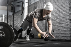 Pushup workout in gym. Strong guy with a beard makes a pushup with a front clap in the gym on the gray brick wall background. He wears sportswear, white sneakers royalty free stock photos