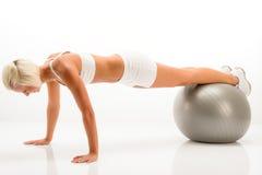 Pushups da esfera da ginástica de mulher na aptidão branca Imagens de Stock Royalty Free