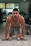 Pushups With Dumbbels. Young Athlete Doing Pushups With Dumbbells As Part Of Bodybuilding Training Royalty Free Stock Images