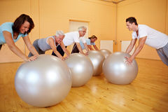 Pushups on exercise ball. Group in gym doing pushups on exercise ball Royalty Free Stock Photos