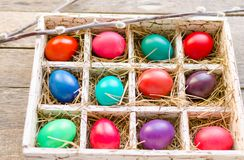 Pussy willows and Easter eggs in a box on old wooden table. Willow twigs and Easter eggs in a wooden box on an old wooden table Royalty Free Stock Photo