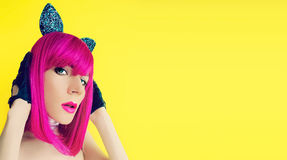 Pussycat lady in bright wig on yellow background. Glamorous party style stock image