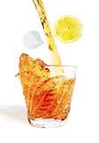 Pust av alkohol häller med färgstänk in i exponeringsglaset med is Arkivfoton
