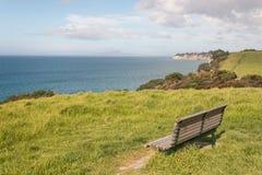 Pusta ławka na zielonej łąkowej above Długiej zatoce Zdjęcie Stock