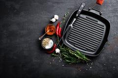 Pusta żeliwna grill niecka z składnikami dla gotować na czarnym tle zdjęcia royalty free