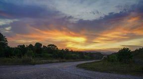 Pusta żwir droga przeciw pomarańczowemu niebu Obraz Royalty Free