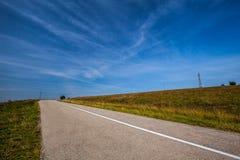 Pusta asfaltowa droga nad polem trawa podczas lata Niebieskie niebo w Zdjęcie Royalty Free
