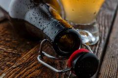 Pusta butelka z szklanym piwem na drewno stole Obraz Royalty Free