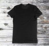Pusta czarna koszulka na drewnianej powierzchni fotografia stock
