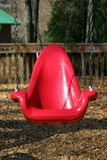 Pusta czerwona wiadro huśtawka przy parkowym boiskiem Zdjęcia Stock