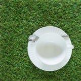 Pusta czysta biała filiżanka na trawy tle Obrazy Royalty Free