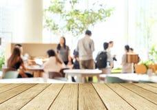 Pusta drewniana perspektywa, stołowy wierzchołek nad plamy grupy ludzi drużyną, obraz stock
